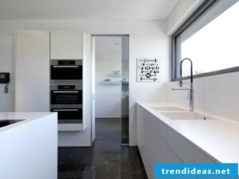 designer white kitchen island and dark floor