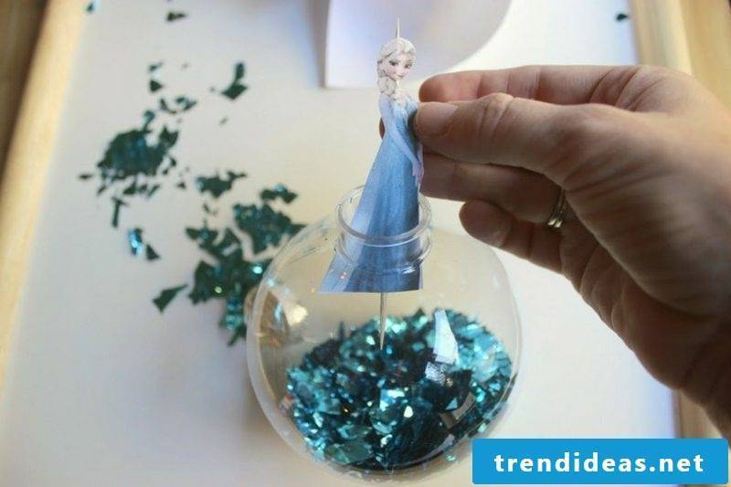 Crafting for Christmas with children Tree decoration Ice queen put the Elsa figure in the ball