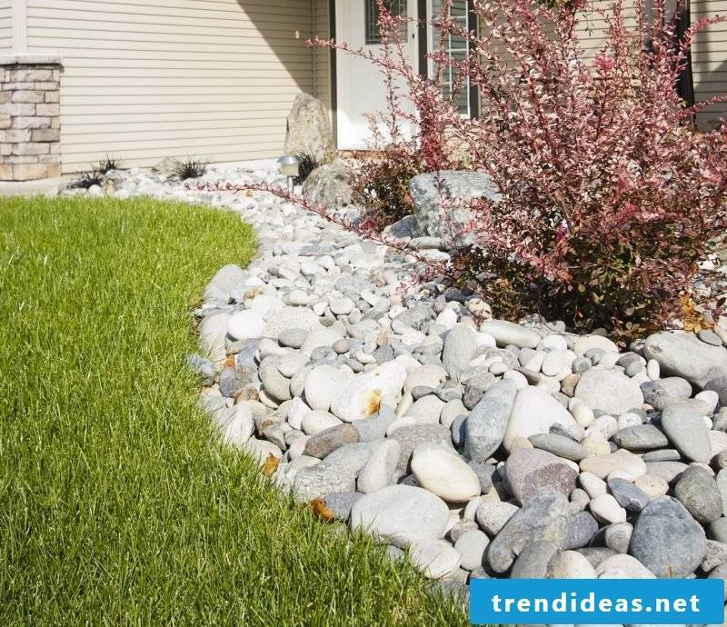 Lay out a bed of stones to create a separation between the path to the house and grass