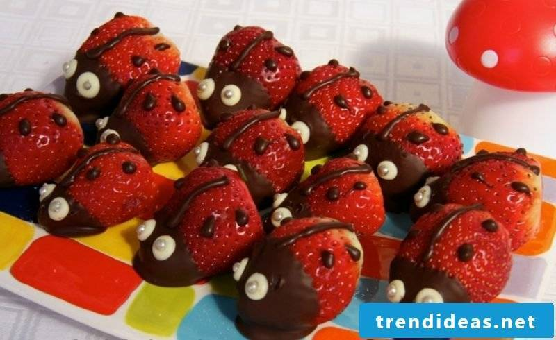 Kids birthday eating strawberries with chocolate ladybugs