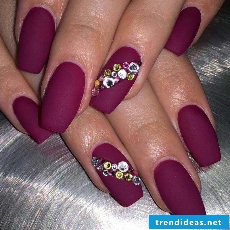 long gel nails in dark red, decorated with rhinestones