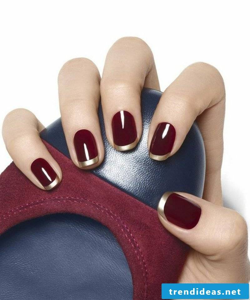 Gel nails in Burgundy red with golden nail edge