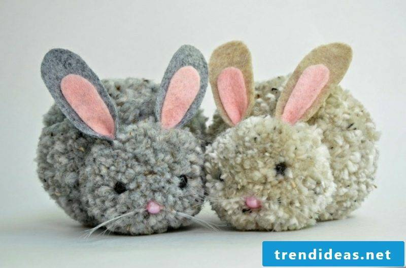 two pompom bunnies made of different yarn