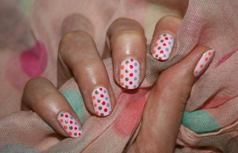 Fingernails with colored dots of pink nail polish