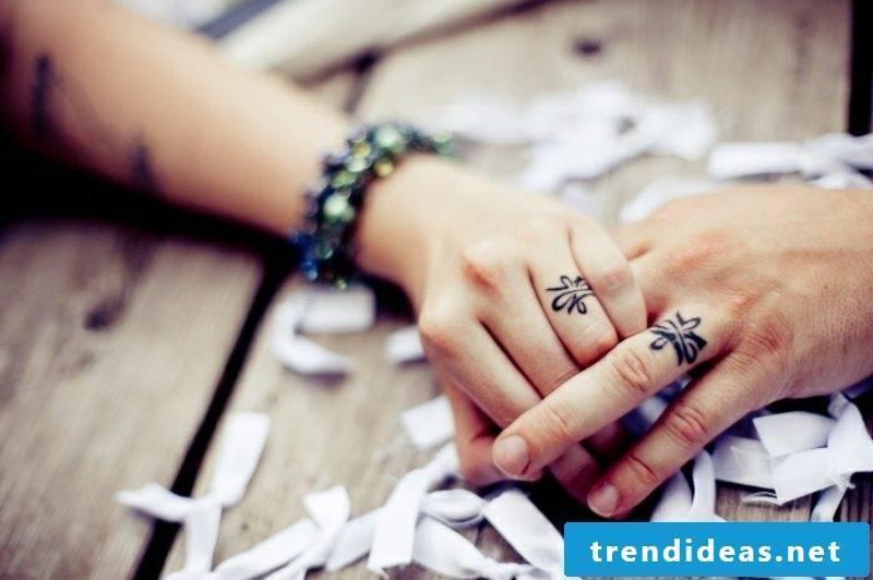 Partner tattoos stylized wedding rings