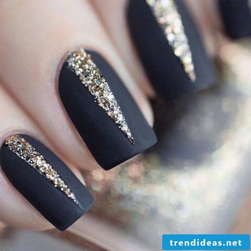 Nail art design autumn paint in black with golden glitter