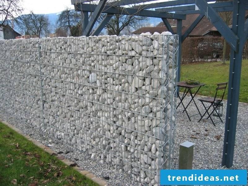 high gabion fence as a screen in the garden