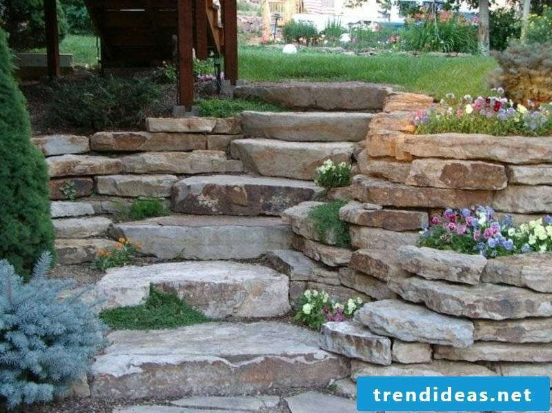 Stone wall in the garden stair flower beds