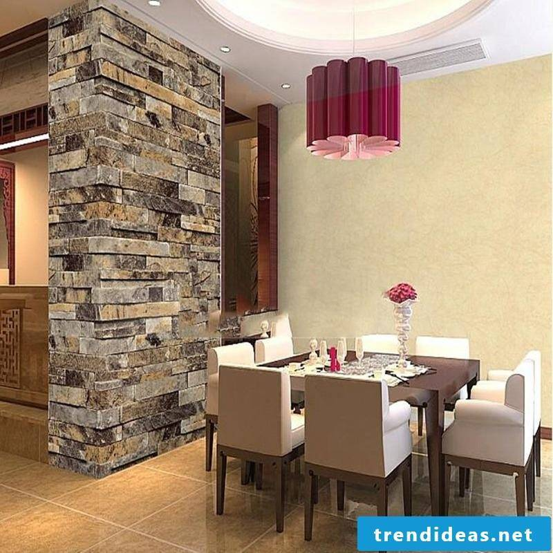 Wall panels with stone look as a separation between dining area and living room