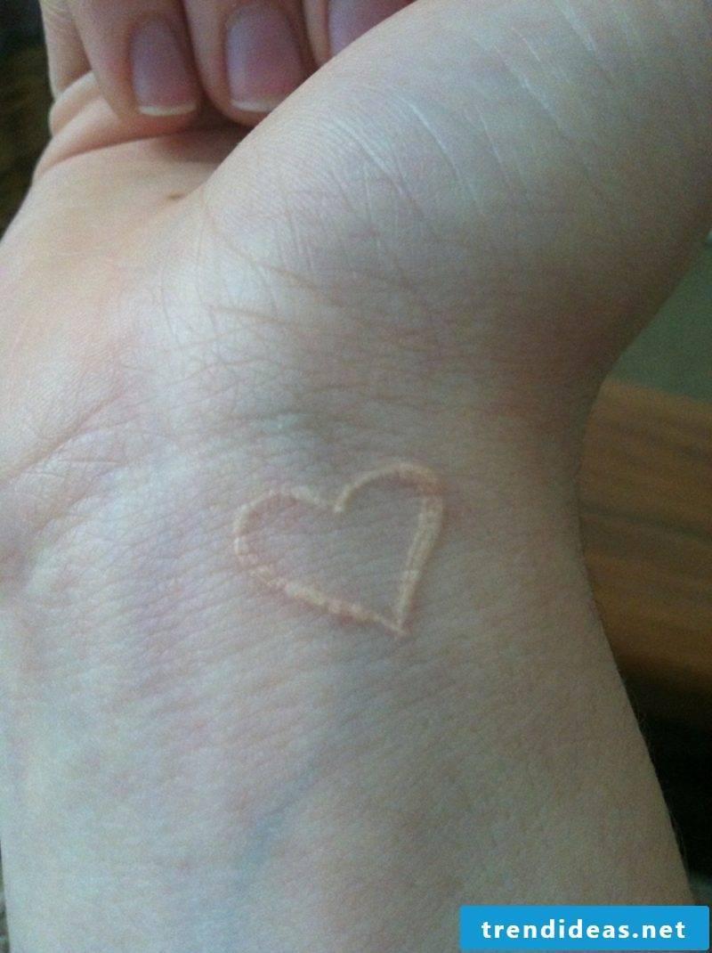 white ink tattoo heart wrist
