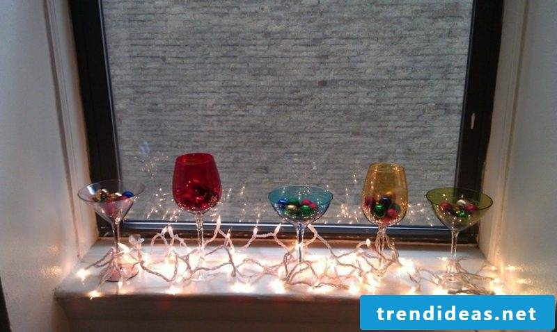 Christmas decoration windowsill colorful glasses, baubles, fairy lights